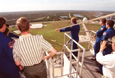 The STS-102 crew watches a slidewire basket speed down the line to the landing area. At left (backs to camera, back to front) are Commander James Wetherbee, Mission Specialists Susan Helms and Paul Richards. At right are (left to right) Mission Specialists Andrew Thomas and James Voss and Pilot James Kelly. Not seen is Mission Specialist Yury Usachev. The crew is taking part in Terminal Countdown Demonstration Test activities, which include the emergency exit training and a simulated launch countdown. STS-102 is the eighth construction flight to the International Space Station, with Space Shuttle Discovery carrying the Multi-Purpose Logistics Module Leonardo. Launch on mission STS-102 is scheduled for March 8
