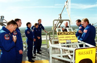 On the Fixed Service Structure on Launch Pad 39B, the STS-102 crew are instructed on the use of slidewire baskets for emergency exits from the launch pad. Listening to the instructor are (on the left side, left to right) Mission Specialist James Voss, Pilot James Kelly, Mission Specialists Yury Usachev and Susan Helms, Commander James Wetherbee; on the right side are Mission Specialists Paul Richards and Andrew Thomas. The crew is taking part in Terminal Countdown Demonstration Test activities, which include a simulated launch countdown. STS-102 is the eighth construction flight to the International Space Station, with Space Shuttle Discovery carrying the Multi-Purpose Logistics Module Leonardo. Voss, Helms and Usachev are the Expedition Two crew who will be the second resident crew on the International Space Station. They will replace Expedition One, who will return to Earth with Discovery. Launch on mission STS-102 is scheduled for March 8