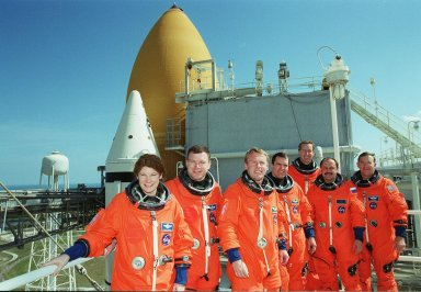 The STS-102 crew poses for a photo on the 215-foot level of the Fixed Service Structure. Behind them is Space Shuttle Discovery. Standing, left to right, are Mission Specialist Susan Helms, Pilot James Kelly, Mission Specialists Andrew Thomas and Paul Richards, Commander James Wetherbee and Mission Specialists Yury Usachev and James Voss. The crew is taking part in Terminal Countdown Demonstration Test activities, which include emergency exit training and a simulated launch countdown. STS-102 is the eighth construction flight to the International Space Station, with Space Shuttle Discovery carrying the Multi-Purpose Logistics Module Leonardo. Voss, Helms and Usachev are the Expedition Two crew who will be the second resident crew on the International Space Station. They will replace Expedition One, who will return to Earth with Discovery. Launch on mission STS-102 is scheduled for March 8