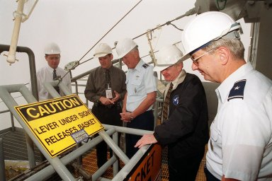 On the Fixed Service Structure on Launch Pad 39B, this distinguished group look at the emergency escape equipment that could be used by astronauts and workers if needed. Gathered around the slidewire basket are Dave King, director of Shuttle Processing; Dave Rainer; Gen. Ralph Everhart, Commander, Space Command; Center Director Roy Bridges; and Brig. Gen. Donald Pettit, Commander of the 45th Space Wing, Cape Canaveral
