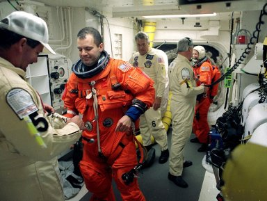 Technicians in the White Room, Launch Pad 39B, help STS-102 Mission Specialist Paul Richards with his launch and entry suit before he enters Space Shuttle Discovery. The mission is Richards? first Shuttle flight. In the background is Mission Specialist Susan Helms. Discovery is carrying the Multi-Purpose Logistics Module Leonardo on the eighth construction flight to the International Space Station. The primary delivery system used to resupply and return Station cargo requiring a pressurized environment, Leonardo will deliver up to 10 tons of laboratory racks filled with equipment, experiments and supplies for outfitting the newly installed U.S. Laboratory Destiny. Discovery is set to launch March 8 at 6:42 a.m. EST. The 12-day mission is expected to end with a landing at KSC on March 20