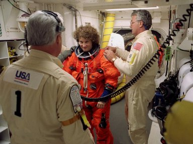 Technicians in the White Room, Launch Pad 39B, help STS-102 Mission Specialist Susan Helms with her launch and entry suit before she enters Space Shuttle Discovery. The mission is Helms? fifth Shuttle flight. Helms is also part of the Expedition Two crew flying on the mission to replace the Expedition One crew on the Station. Discovery is carrying the Multi-Purpose Logistics Module Leonardo on the eighth construction flight to the International Space Station. The primary delivery system used to resupply and return Station cargo requiring a pressurized environment, Leonardo will deliver up to 10 tons of laboratory racks filled with equipment, experiments and supplies for outfitting the newly installed U.S. Laboratory Destiny. Discovery is set to launch March 8 at 6:42 a.m. EST. The 12-day mission is expected to end with a landing at KSC on March 20