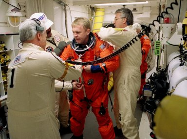Before entering Space Shuttle Discovery, STS-102 Mission Specialist Andrew Thomas is helped with his launch and entry suit by technicians in the White Room. The mission is Thomas?s third Shuttle flight. Discovery is carrying the Multi-Purpose Logistics Module Leonardo on the eighth construction flight to the International Space Station. The primary delivery system used to resupply and return Station cargo requiring a pressurized environment, Leonardo will deliver up to 10 tons of laboratory racks filled with equipment, experiments and supplies for outfitting the newly installed U.S. Laboratory Destiny. Discovery is set to launch March 8 at 6:42 a.m. EST. The 12-day mission is expected to end with a landing at KSC on March 20