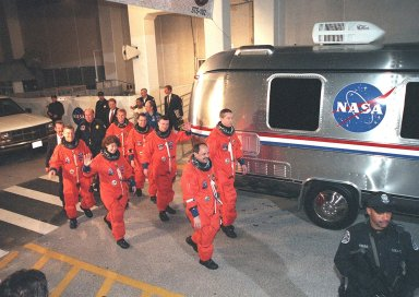 The STS-102 crew heads for the Astrovan after leaving the Operations and Checkout Building behind them. In front, left to right, are Mission Specialists James Voss, Susan Helms and Yury Usachev. In back, left to right, are Mission Specialists Andrew Thomas and Paul Richards, Pilot James Kelly and Commander James Wetherbee. STS-102 is the eighth construction flight to the Space Station, carrying the Multi-Purpose Logistics Module Leonardo. The primary delivery system used to resupply and return Station cargo requiring a pressurized environment, Leonardo will deliver up to 10 tons of laboratory racks filled with equipment, experiments and supplies for outfitting the newly installed U.S. Laboratory Destiny. In addition, Voss, Helms and Usachev, known as Expedition Two, are flying to the Station to replace Expedition One, who will return to Earth on Discovery. Discovery is set to launch March 8 at 6:42 a.m. EST. The 12-day mission is expected to end with a landing at KSC on March 20