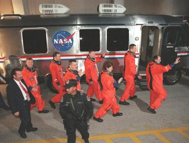 The STS-102 crew wave to onlookers as they head for the Astrovan after leaving the Operations and Checkout Building. Left to right are Mission Specialists Andrew Thomas, Paul Richards and James Voss; Pilot James Kelly; Mission Specialist Susan Helms; Commander James Wetherbee; and Mission Specialist Yury Usachev. STS-102 is the eighth construction flight to the Space Station, carrying the Multi-Purpose Logistics Module Leonardo. The primary delivery system used to resupply and return Station cargo requiring a pressurized environment, Leonardo will deliver up to 10 tons of laboratory racks filled with equipment, experiments and supplies for outfitting the newly installed U.S. Laboratory Destiny. In addition, Voss, Helms and Usachev, known as Expedition Two, are flying to the Station to replace Expedition One, who will return to Earth on Discovery. Discovery is set to launch March 8 at 6:42 a.m. EST. The 12-day mission is expected to end with a landing at KSC on March 20