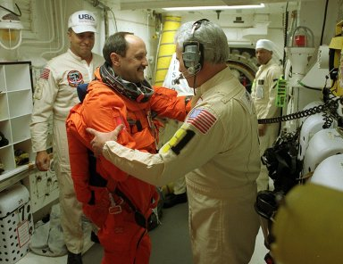 In the White Room, Launch Pad 39B, STS-102 Mission Specialist Yury Usachev gets warm greetings from one of the suit technicians helping with final preparations before entering Space Shuttle Discovery. STS-102 is Russian cosmonaut Usachev?s second Shuttle flight. He is also part of the Expedition Two crew flying on the mission to replace the Expedition One crew on the Station. Discovery is carrying the Multi-Purpose Logistics Module Leonardo on the eighth construction flight to the International Space Station. The primary delivery system used to resupply and return Station cargo requiring a pressurized environment, Leonardo will deliver up to 10 tons of laboratory racks filled with equipment, experiments and supplies for outfitting the newly installed U.S. Laboratory Destiny. Discovery is set to launch March 8 at 6:42 a.m. EST. The 12-day mission is expected to end with a landing at KSC on March 20