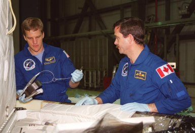 STS-100 Mission Specialists Scott Parazynski (left) and Chris Hadfield (right), who is with the Canadian Space Agency, look over equipment that will be used during their mission. They are taking part in a Crew Equipment Interface Test (CEIT) at KSC, along with other crew members Commander Kent V. Rominger, Pilot Jeffrey S. Ashby and Mission Specialists John L. Phillips, Umberto Guidoni, who is with the European Space Agency, and Yuri Lonchakov, who is with the Russian Aviation and Space Agency. The orbiter is also carrying the Multi-Purpose Logistics Module Raffaello to the International Space Station. Raffaello carries six system racks and two storage racks for the U.S. Lab. Launch of mission STS-100 is scheduled for April 19 at 2:41 p.m. EDT from Launch Pad 39A