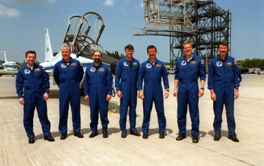 The STS-100 crew poses for a photo after landing at the Shuttle Landing Facility. They are at KSC to take part in Terminal Countdown Demonstration Test activities, from emergency escape training at the pad to a simulated launch countdown. Standing, left to right, are Mission Specialists Yuri Lonchakov, John Phillips, Umberto Guidoni; Pilot Jeff Ashby; Mission Specialists Chris Hadfield and Scott Parazynski; and Commander Kent Rominger. The mission is carrying the Multi-Purpose Logistics Module Raffaello and the Canadian robotic arm, SSRMS, to the International Space Station. Raffaello carries six system racks and two storage racks for the U.S. Lab. The SSRMS is crucial to the continued assembly of the orbiting complex and has a unique ability to switch ends as it works, ?inchworming? along the Station?s exterior. Launch of mission STS-100 is scheduled for April 19 at 2:41 p.m. EDT from Launch Pad 39A