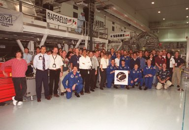 The STS-100 crew gathers with the Space Station Processing Facility people who worked on the Canadian robotic arm, SSRMS. Kneeling at left is Commander Kent V. Rominger; front and ceneter, from left, Mission Specialist Chris Hadfield, Pilot Jeffrey S. Ashby and Mission Specialists Yuri V. Lonchakov and John L. Phillips; behind Hadfield (a head above the others) is Mission Specialist Scott E. Parazynski. The crew is at KSC for Terminal Countdown Demonstration Test activities that include emergency escape training at the pad and a simulated launch countdown. The mission is carrying the Multi-Purpose Logistics Module Raffaello and the SSRMS, to the International Space Station. Raffaello carries six system racks and two storage racks for the U.S. Lab. The SSRMS is crucial to the continued assembly of the orbiting complex. Launch of mission STS-100 is scheduled for April 19 at 2:41 p.m. EDT from Launch Pad 39A