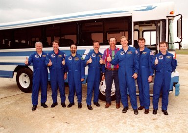 The STS-100 crew gathers at the bus when Terminal Countdown Demonstration Test activities are hampered by the rain. Standing with the bus driver, from left, are Mission Specialist John L. Phillips, Commander Kent V. Rominger, Mission Specialists Umberto Guidoni, Chris Hadfield, [driver], and Scott E. Parazynski, Pilot Jeffrey S. Ashby and Mission Specialist Yuri V. Lonchakov. TCDT includes emergency escape training at the pad and a simulated launch countdown. The mission is carrying the Multi-Purpose Logistics Module Raffaello and the Canadian robotic arm, SSRMS, to the International Space Station. Raffaello carries six system racks and two storage racks for the U.S. Lab. The SSRMS is crucial to the continued assembly of the orbiting complex. Launch of mission STS-100 is scheduled for April 19 at 2:41 p.m. EDT from Launch Pad 39A