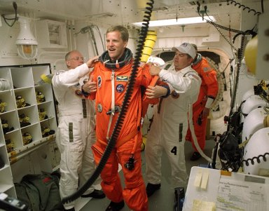 KENNEDY SPACE CENTER, FLA. -- In the White Room, STS-100 Mission Specialist Scott Parazynski is helped with his launch and entry suit by the closeout crew. The White Room is an environmental chamber at the end of the Orbiter Access Arm that provides entry into the orbiter on the launch pad. The mission will deliver and integrate the Spacelab Logistics Pallet/Launch Deployment Assembly, which includes the Canadian-built Space Station Remote Manipulator System and the UHF Antenna. Two spacewalks are planned for installation of the SSRMS, which will be performed by Mission Specialists Parazynski and Chris Hadfield, who is with the Canadian Space Agency. The mission is also the inaugural flight of Multi-Purpose Logistics Module Raffaello, carrying resupply stowage racks and resupply/return stowage platforms. Liftoff of Space Shuttle Endeavour on mission STS-100 is scheduled at 2:41 p.m. EDT April 19.