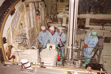 KENNEDY SPACE CENTER, FLA. -- During Crew Equipment Interface Test activities in Orbiter Processing Facility bay 2, members of the STS-105 crew check out some of the payload, doing sharp edge inspection. From left are Mission Specialists Patrick Forrester and Daniel Barry, accompanied by a Boeing technician (behind) and the bucket operator (right). STS-105 is the 11th mission to the International Space Station. The payload includes the Multi-Purpose Logistics Module Leonardo, which was built by the Italian Space Agency. Leonardo will be outfitted with 12 racks of experiments and equipment. Discovery is scheduled to launch July 12 from Launch Pad 39A