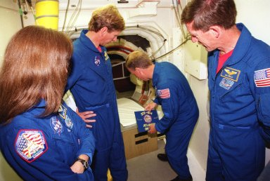 KENNEDY SPACE CENTER, Fla. -- In the White Room at Launch Pad 39B, Commander Steven W. Lindsey places a crew patch at the entrance to Space Shuttle Atlantis while other crew members look on. At left are Mission Specialists Janet Lynn Kavandi and Michael L. Gernhardt, and at right is Mission Specialist James F. Reilly. Not seen is Pilot Charles O. Hobaugh. The crew is taking part in Terminal Countdown Demonstration Test activities, which include emergency exit training from the orbiter, opportunities to inspect their mission payloads in the orbiter?s payload bay and simulated countdown exercises. The launch of Atlantis on mission STS-104 is scheduled July 12 from Launch Pad 39B. The mission is the 10th flight to the International Space Station and carries the Joint Airlock Module