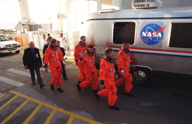 KENNEDY SPACE CENTER, Fla. -- Dressed in their orange launch and entry suits, the STS-104 crew eagerly walk to the Astrovan that will take them to Launch Pad 39B and a simulated countdown exercise. From left are Mission Specialists Michael L. Gernhardt, James F. Reilly and Janet Lynn Kavandi; Commander Steven W. Lindsey and Pilot Charles O. Hobaugh. The crew is taking part in Terminal Countdown Demonstration Test activities, which include emergency exit training from the orbiter, opportunities to inspect their mission payloads in the orbiter?s payload bay and simulated countdown exercises. The launch of Atlantis on mission STS-104 is scheduled July 12 from Launch Pad 39B. The mission is the 10th flight to the International Space Station and carries the Joint Airlock Module
