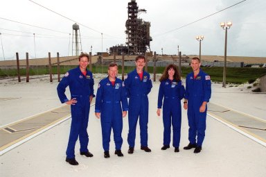 KENNEDY SPACE CENTER, Fla. -- The STS-104 crew poses for a photo in the slidewire basket grounds near Launch Pad 39B and Space Shuttle Atlantis (behind them). Standing left to right are Mission Specialist Michael L. Gernhardt, Commander Steven W. Lindsey, Mission Specialists James F. Reilly and Janet Lynn Kavandi, and Pilot Charles O. Hobaugh. The crew is taking part in Terminal Countdown Demonstration Test activities, which include emergency exit training, opportunities to inspect their mission payloads in the orbiter?s payload bay and simulated countdown exercises. The launch of Atlantis on mission STS-104 is scheduled July 12 from Launch Pad 39B. The mission is the 10th flight to the International Space Station and carries the Joint Airlock Module