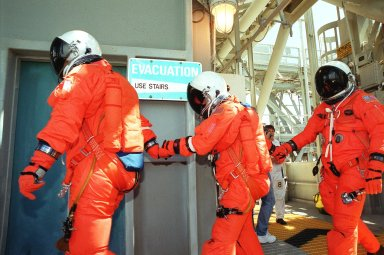 KENNEDY SPACE CENTER, Fla. -- On Launch Pad 39B, dressed in their launch and entry suits, STS-104 Mission Specialists (left to right) James F. Reilly, Janet Lynn Kavandi and Michael L. Gernhardt make their way from Space Shuttle Atlantis to the slidewire baskets, part of the emergency egress system at the pad. They and other crew members are taking part in Terminal Countdown Demonstration Test activities, which include the emergency egress training and a simulated countdown exercise. The launch of Atlantis on mission STS-104 is scheduled July 12. The mission is the 10th flight to the International Space Station and carries the Joint Airlock Module and High Pressure Gas Assembly