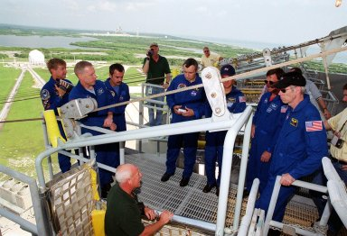 KENNEDY SPACE CENTER, Fla. -- On the 195-foot level of the Fixed Service Structure, Launch Pad 39A, the STS-105 and Expedition Three crews listen to instructions about use of the slidewire basket, part of emergency egress training at the pad. From left are Expedition Three Commander Frank Culbertson, STS-105 Pilot Rick Sturckow; cosmonauts Mikhail Tyurin and Vladimir Nikolaevich Dezhurov; Mission Specialist Patrick Forrester, Commander Scott Horowitz and Mission Specialist Daniel Barry. Both crews are at KSC to take part in Terminal Countdown Demonstration Test activities, which include the emergency egress training, a simulated launch countdown and familiarization with the payload. Mission STS-105 will be transporting the Expedition Three crew, several payloads and scientific experiments to the International Space Station aboard Discovery. The current Expedition Two crew members on the Station will return to Earth on Discovery. Launch of Discovery is scheduled no earlier than Aug. 9, 2001