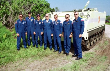 KENNEDY SPACE CENTER, Fla. -- The STS-105 and Expedition Three crews pose in front of the M-113 armored personnel carrier that is part of emergency egress training at the pad. From left to right, they are STS-105 Commander Scott Horowitz, Mission Specialist Daniel Barry, Pilot Rick Sturckow, and Mission Specialist Patrick Forrester; Expedition Three Commander Frank Culbertson and cosmonauts Mikhail Tyurin and Vladimir Nikolaevich Dezhurov. The training is part of Terminal Countdown Demonstration Test activities, which also include a simulated launch countdown and familiarization with the payload. Mission STS-105 will be transporting the Expedition Three crew, several payloads and scientific experiments to the International Space Station aboard Space Shuttle Discovery. The current Expedition Two crew members on the Station will return to Earth on Discovery. Launch of Discovery is scheduled no earlier than Aug. 9, 2001