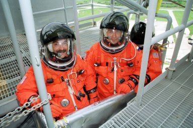 KENNEDY SPACE CENTER, Fla. -- Expedition Three cosmonaut Mikhail Tyurin (left), Commander Frank Culbertson (center) and cosmonaut Vladimir Nikolaevich Dezhurov (right) pose for a photo inside the slidewire basket that is part of the emergency egress system. They and the STS-105 crew are at Kennedy Space Center participating in a Terminal Countdown Demonstration Test, a dress rehearsal for launch. The activities also include a simulated launch countdown and familiarization with the payload. Mission STS-105 will be transporting the Expedition Three crew, several payloads and scientific experiments to the International Space Station aboard Space Shuttle Discovery. The Expedition Two crew members currently on the Station will return to Earth on Discovery. The mission is scheduled to launch no earlier than Aug. 9, 2001