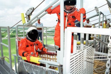 KENNEDY SPACE CENTER, Fla. -- STS-105 Pilot Rick Sturckow (left) waits for Commander Scott Horowitz (right) to climb into the slidewire basket that is part of the emergency egress system. The STS-105 and Expedition Three crews are at Kennedy Space Center participating in a Terminal Countdown Demonstration Test, a dress rehearsal for launch. The activities also include a simulated launch countdown and familiarization with the payload. Mission STS-105 will be transporting the Expedition Three crew, several payloads and scientific experiments to the International Space Station aboard Space Shuttle Discovery. The Expedition Two crew members currently on the Station will return to Earth on Discovery. The mission is scheduled to launch no earlier than Aug. 9, 2001