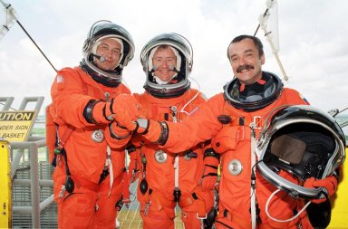 KENNEDY SPACE CENTER, Fla. -- The Expedition Three crew join hands for a photo on Launch Pad 39A. From left are cosmonaut Vladimir Nikolaevich Dezhurov, Commander Frank Culbertson and cosmonaut Mikhail Tyurin. The STS-105 and Expedition Three crews are at Kennedy Space Center participating in a Terminal Countdown Demonstration Test, a dress rehearsal for launch. The activities include emergency egress training, a simulated launch countdown and familiarization with the payload. Mission STS-105 will be transporting the Expedition Three crew, several payloads and scientific experiments to the International Space Station aboard Space Shuttle Discovery. The Expedition Two crew members currently on the Station will return to Earth on Discovery. The mission is scheduled to launch no earlier than Aug. 9, 2001