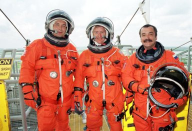 KENNEDY SPACE CENTER, Fla. -- The Expedition Three crew poses for a photo on Launch Pad 39A. From left are cosmonaut Vladimir Nikolaevich Dezhurov, Commander Frank Culbertson and cosmonaut Mikhail Tyurin. The STS-105 and Expedition Three crews are at Kennedy Space Center participating in a Terminal Countdown Demonstration Test, a dress rehearsal for launch. The activities include emergency egress training, a simulated launch countdown and familiarization with the payload. Mission STS-105 will be transporting the Expedition Three crew, several payloads and scientific experiments to the International Space Station aboard Space Shuttle Discovery. The Expedition Two crew members currently on the Station will return to Earth on Discovery. The mission is scheduled to launch no earlier than Aug. 9, 2001