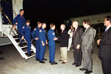 KENNEDY SPACE CENTER, Fla. -- The STS-104 crew exits the Crew Transport Vehicle after completing the 10th assembly flight aboard Atlantis to the International Space Station. Commander Steven Lindsey is welcomed home by Center Director Roy Bridges (center). Lined up behind Lindsey (right to left) are Pilot Charles Hobaugh and Mission Specialists Michael Gernhardt, Janet Lynn Kavandi and James Reilly. Atlantis touched down at 11:38:55 p.m. EDT July 24, 2001, completing a 12-day, 18-hour, 34-minute-long mission to the International Space Station. The mission delivered the Joint Airlock Module to the Space Station, completing the second phase of the assembly of the Space Station. This is the 18th nighttime landing for a Space Shuttle, the 13th at Kennedy Space Center
