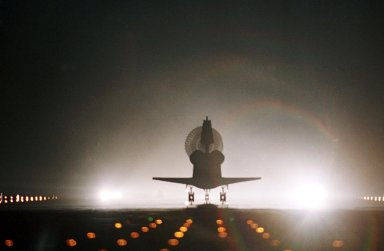 KENNEDY SPACE CENTER, Fla. -- Runway lights cast a rainbow from the colors in the drag chute behind Atlantis as it lands at the Shuttle Landing Facility. Main gear touchdown occurred at 11:38:55 p.m. EDT, completing complete a 12-day, 18-hour, 34-minute-long STS-104 mission. At the controls is Commander Steven W. Lindsey. Other crew members on board are Pilot Charles Hobaugh and Mission Specialists Michael Gernhardt, Janet Lynn Kavandi and James F. Reilly. This is the 18th nighttime landing for a Space Shuttle, the 13th at Kennedy Space Center. The mission delivered the Joint Airlock Module to the International Space Station, completing the second phase of the assembly of the Space Station