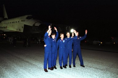 KENNEDY SPACE CENTER, Fla. -- The STS-104 crew wave at onlookers who welcomed them home from their almost 13-day mission to the International Space Station. From left are Mission Specialists James Reilly and Janet Lynn Kavandi, Commander Steven Lindsey, Pilot Charles Hobaugh and Mission Specialist Michael Gernhardt. Atlantis touched down at 11:38:55 p.m. EDT July 24, 2001. The mission delivered the Joint Airlock Module to the Space Station, completing the second phase of the assembly of the Space Station. This is the 18th nighttime landing for a Space Shuttle, the 13th at Kennedy Space Center