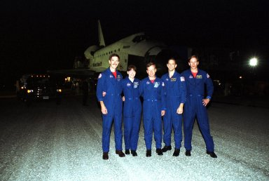 KENNEDY SPACE CENTER, Fla. -- After a perfect landing at the Shuttle Landing Facility, the STS-104 crew poses for a photo. Standing in front of Atlantis are Mission Specialists James Reilly and Janet Lynn Kavandi, Commander Steven Lindsey, Pilot Charles Hobaugh and Mission Specialist Michael Gernhardt. Atlantis touched down at 11:38:55 p.m. EDT July 24, 2001, completing a 12-day, 18-hour, 34-minute-long mission to the International Space Station. The mission delivered the Joint Airlock Module to the Space Station, completing the second phase of the assembly of the Space Station. This is the 18th nighttime landing for a Space Shuttle, the 13th at Kennedy Space Center
