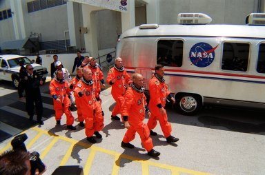 KENNEDY SPACE CENTER, Fla. -- The STS-105 crew eagerly leads the way to the Astrovan, followed by the Expedition Three (E3) crew, and the drive to Launch Pad 39A for launch. Leading the way are Pilot Rick Sturckow (near) and Commander Scott Horowitz; in the second row, Mission Specialists Patrick Forrester (near) and Daniel Barry; in the third row, E3 cosmonaut Mikhail Tyurin (left), Commander Frank Culbertson (center), and cosmonaut Vladimir Dezhurov (right). Forrester and Tyurin are both making their first space flights. On the mission, Discovery will be transporting the Expedition Three crew and several payloads and scientific experiments to the ISS, including the Early Ammonia Servicer (EAS) tank. The EAS, which will support the thermal control subsystems until a permanent system is activated, will be attached to the Station during two spacewalks. The three-member Expedition Two crew will be returning to Earth aboard Discovery after a five-month stay on the Station. Launch is scheduled for 5:38 p.m. EDT Aug. 9