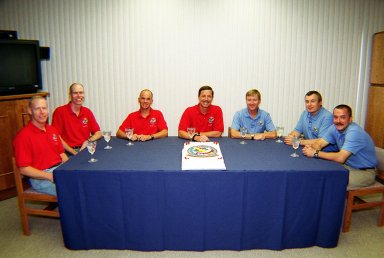 KENNEDY SPACE CENTER, Fla. -- Before suitup, the STS-105 and Expedition Three crews celebrate the pending launch with a special cake. In red shirts, seated left to right, are STS-105 Mission Specialists Patrick Forrester and Daniel Barry, Pilot Rick Sturckow and Commander Scott Horowitz. In blue shirts are the Expedition Three crew, Commander Frank Culbertson, Vladimir Dezhurov and Mikhail Tyurin. Dezhurov and Tyurin are cosmonauts with the Russian Aviation and Space Agency. On the mission, Discovery will be transporting the Expedition Three crew and several payloads and scientific experiments to the ISS, including the Early Ammonia Servicer (EAS) tank. The EAS, which will support the thermal control subsystems until a permanent system is activated, will be attached to the Station during two spacewalks. The three-member Expedition Two crew will be returning to Earth aboard Discovery after a five-month stay on the Station. Launch is scheduled for 5:38 p.m. EDT Aug. 9