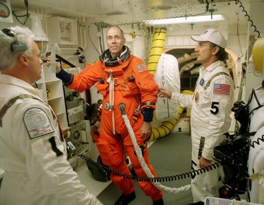 KENNEDY SPACE CENTER, Fla. -- STS-105 Commander Scott Horowitz sends a message home while preparing to enter Space Shuttle Discovery for launch. Assisting with flight equipment are (left) Orbiter Vehicle Closeout Chief Chris Meinert, (right) USA Mechanical Technician Al Schmidt and (behind) NASA Quality Assurance Specialist Ken Strite. The payload on the STS-105 mission to the International Space Station includes the third flight of the Italian-built Multi-Purpose Logistics Module Leonardo, delivering additional scientific racks, equipment and supplies for the Space Station, and the Early Ammonia Servicer (EAS) tank. The EAS, which will be attached to the Station during two spacewalks, contains spare ammonia for the Station's cooling system. Also, the Expedition Three crew is aboard to replace the Expedition Two crew on the Space Station, who will be returning to Earth aboard Discovery after a five-month stay on the Station