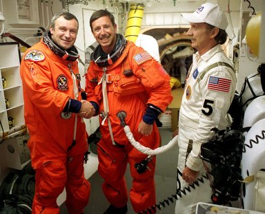 KENNEDY SPACE CENTER, Fla. - Expedition Three crew member Vladimir Dezhurov (left) is ready for his first space flight, under the guidance of STS-105 Commander Scott Horowitz (center). Helping with flight equipment before launch is (right) USA Mechanical Technician Al Schmidt. The payload on the STS-105 mission to the International Space Station includes the third flight of the Italian-built Multi-Purpose Logistics Module Leonardo, delivering additional scientific racks, equipment and supplies for the Space Station, and the Early Ammonia Servicer (EAS) tank. The EAS, which will be attached to the Station during two spacewalks, contains spare ammonia for the Station?s cooling system. Also, the Expedition Three crew is aboard to replace the Expedition Two crew on the International Space Station, who will be returning to Earth aboard Discovery after a five-month stay on the Station