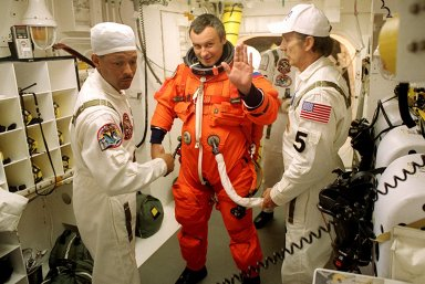KENNEDY SPACE CENTER, Fla. - Expedition Three crew member Vladimir Dezhurov waves as he is helped with his launch and entry suit before he enters Space Shuttle Discovery for launch. Helping him are (left) NASA Astronaut Support Personnel John Herrington and (right) USA Mechanical Technician Al Schmidt. The payload on the STS-105 mission to the International Space Station includes the third flight of the Italian-built Multi-Purpose Logistics Module Leonardo, delivering additional scientific racks, equipment and supplies for the Space Station, and the Early Ammonia Servicer (EAS) tank. The EAS, which will be attached to the Station during two spacewalks, contains spare ammonia for the Station?s cooling system. Also, the Expedition Three crew is aboard to replace the Expedition Two crew on the International Space Station, who will be returning to Earth aboard Discovery after a five-month stay on the Station