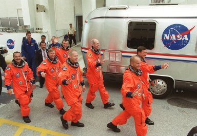 KENNEDY SPACE CENTER, Fla. -- Waving to onlookers, the STS-105 and Expedition Three (E3) crews head to the Astrovan that will take them to Launch Pad 39A for a second attempt at launch on mission STS-105. From the left are E3 cosmonaut Mikhail Tyurin, Commander Frank Culbertson and cosmonaut Vladimir Dezhurov; STS-105 Mission Specialists Patrick Forrester and Daniel Barry, Pilot Rick Sturckow and Commander Scott Horowitz. . Launch countdown activities for the 12-day mission were called off at about 5:12 p.m. Aug. 9 during the T-9 minute hold due to the high potential for lightning, a thick cloud cover and the potential for showers. Launch is currently scheduled for 5:15 p.m. EDT Aug. 10. Highlighting the mission will be the rotation of the International Space Station crew, the third flight of an Italian-built Multi-Purpose Logistics Module delivering additional scientific racks, equipment and supplies for the Space Station, and two spacewalks. Included in the payload is the Early Ammonia Servicer (EAS) tank, which will be attached to the Station during the spacewalks. The EAS will be installed on the P6 truss, which holds the Station?s giant U.S. solar arrays, batteries and the cooling radiators. The EAS contains spare ammonia for the Station?s cooling system. The three-member Expedition Two crew will be returning to Earth aboard Discovery after a five-month stay on the Station
