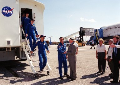 """KENNEDY SPACE CENTER, Fla. - As members of the STS-105 crew exit the Crew Transfer Vehicle (CTV) following Discovery's landing on KSC's Shuttle Landing Facility runway 15, they are greeted by NASA Administrator Dan Goldin. From left are Mission Specialists Patrick Forrester and Daniel Barry, Pilot Frederick """"Rick"""" Sturckow, and Commander Scott """"Doc"""" Horowitz (shaking hands with Goldin). Looking on are, from left, Kathie Olsen, NASA chief scientist; Joe Rothenberg, associate administrator, Office of Space Flight; and Courtney Stadd, NASA Headquarters chief of staff. Main gear touchdown was at 2:22:58 p.m. EDT; wheel stop, at 2:24:06 p.m. EDT. The 11-day, 21-hour, 12-minute STS-105 mission accomplished the goals set for the 11th flight to the International Space Station: swapout of the resident Station crew; delivery of equipment, supplies and scientific experiments; and installation of the Early Ammonia Servicer and heater cables for the S0 truss on the Station. Discovery traveled 4.3 million miles on its 30th flight into space, the 106th mission of the Space Shuttle program. Out of five missions in 2001, the landing was the first to occur in daylight at KSC."""