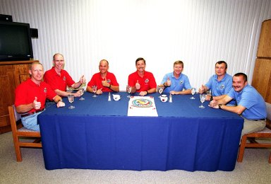 KENNEDY SPACE CENTER, Fla. -- The STS-105 and Expedition Three crews give thumbs up on another opportunity to launch after a 24-hour weather delay. In red shirts, seated left to right, are STS-105 Mission Specialists Patrick Forrester and Daniel Barry, Pilot Rick Sturckow and Commander Scott Horowitz. In blue shirts are the Expedition Three crew, Commander Frank Culbertson, Vladimir Dezhurov and Mikhail Tyurin. Dezhurov and Tyurin are cosmonauts with the Russian Aviation and Space Agency. Highlighting the mission will be the rotation of the International Space Station crew, the third flight of an Italian-built Multi-Purpose Logistics Module delivering additional scientific racks, equipment and supplies for the Space Station, and two spacewalks. Included in the payload is the Early Ammonia Servicer (EAS) tank, which will be attached to the Station during the spacewalks. The EAS will be installed on the P6 truss, which holds the Station?s giant U.S. solar arrays, batteries and the cooling radiators. The EAS contains spare ammonia for the Station?s cooling system. The three-member Expedition Two crew will be returning to Earth aboard Discovery after a five-month stay on the Station. Launch is scheduled for 5:15 p.m. EDT Aug. 10