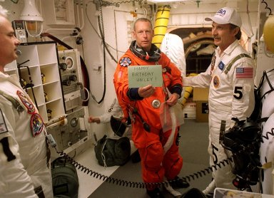 KENNEDY SPACE CENTER, Fla. -- In the White Room, Launch Pad 39A, STS-105 Mission Specialist Patrick Forrester sends a silent greeting home while having his flight equipment checked before entering Space Shuttle Discovery for launch. With him are (left) Orbiter Vehicle Closeout Chief Chris Meinert and USA Mechanical Technician Al Schmidt. In the background is STS-105 Mission Specialist Patrick Forrester. The payload on the STS-105 mission to the International Space Station includes the third flight of the Italian-built Multi-Purpose Logistics Module Leonardo, delivering additional scientific racks, equipment and supplies for the Space Station, and the Early Ammonia Servicer (EAS) tank. The EAS, which will be attached to the Station during two spacewalks, contains spare ammonia for the Station's cooling system. Also, the Expedition Three crew is aboard to replace the Expedition Two crew on the International Space Station, who will be returning to Earth aboard Discovery after a five-month stay on the Station