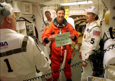 KENNEDY SPACE CENTER, Fla. - STS-105 Commander Scott Horowitz sends a message home while preparing to enter Space Shuttle Discovery for launch. Assisting with flight equipment are (left) Orbiter Vehicle Closeout Chief Chris Meinert, (right) USA Mechanical Technician Al Schmidt and (behind) NASA Quality Assurance Specialist Ken Strite. The payload on the STS-105 mission to the International Space Station includes the third flight of the Italian-built Multi-Purpose Logistics Module Leonardo, delivering additional scientific racks, equipment and supplies for the Space Station, and the Early Ammonia Servicer (EAS) tank. The EAS, which will be attached to the Station during two spacewalks, contains spare ammonia for the Station?s cooling system. Also, the Expedition Three crew is aboard to replace the Expedition Two crew on the International Space Station, who will be returning to Earth aboard Discovery after a five-month stay on the Station