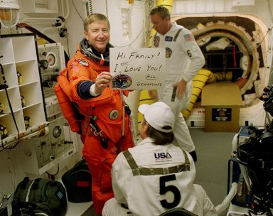 KENNEDY SPACE CENTER, Fla. - Expedition Three Commander Frank Culbertson sends a greeting home while having his flight equipment checked before he enters Space Shuttle Discovery for launch. Helping him are (front) USA Mechanical Technician Al Schmidt and (back) NASA Quality Assurance Specialist Ken Strite. The payload on the STS-105 mission to the International Space Station includes the third flight of the Italian-built Multi-Purpose Logistics Module Leonardo, delivering additional scientific racks, equipment and supplies for the Space Station, and the Early Ammonia Servicer (EAS) tank. The EAS, which will be attached to the Station during two spacewalks, contains spare ammonia for the Station?s cooling system. Also, the Expedition Three crew is aboard to replace the Expedition Two crew on the International Space Station, who will be returning to Earth aboard Discovery after a five-month stay on the Station