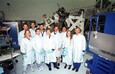 """KENNEDY SPACE CENTER, Fla. -- The STS-111 crew spend time in the Space Station Processing Facility learning more about the payload they will be transporting: The Mobile Base System (MBS). Standing left to right in the back row are Expedition Five Commander Valeri Kozun, with the Russian Aviation and Space Agency; Mission Specialist Phillippe Perrin, with the French space agency CNES; Pilot Paul Lockhart; trainer Chris Hardcastle; Mission Specialist Franklin Chang-Diaz; and Commander Ken Cockrell. Flanked by trainers in the front row is (center) Peggy Whitson, another of the Expedition Five crew who will ferried to the International Space Station. The MBS will be installed on the Mobile Transporter to complete the Canadian Mobile Servicing System, or MSS. The mechanical arm will then have the capability to """"inchworm"""" from the U.S. Lab Destiny to the MSS and travel along the Truss to work sites. The Expedition Five crew will be replacing Expedition Four. Launch of Endeavour on mission STS-111 is scheduled for April 18, 2002"""