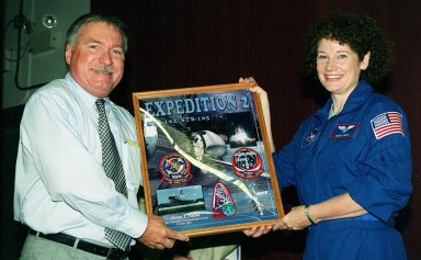 """KENNEDY SPACE CENTER, Fla. - J.J. """"Tip"""" Talone Jr., director of KSC's International Space Station/Payload Processing, presents Expedition 2 crew member Susan Helms with a photo plaque from employees commemorating her stay aboard the Space Station. The Expedition 2 crew, which included astronaut Jim Voss and cosmonaut Yury Usachev, made the space voyage to the Station on mission STS-102 in March 2001. After five months on the Station, they returned to Earth, at the KSC Shuttle Landing Facility, on mission STS-105 in August 2001"""