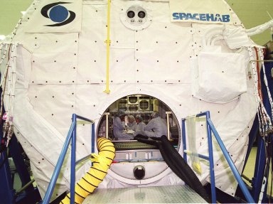 KENNEDY SPACE CENTER, Fla. -- At SPACEHAB,Cape Canaveral, the SPACEHAB Double Module is the site for equipment familiarization for some STS-107 crew members inside. The crew comprises Commander Rick Husband, Pilot William McCool, Payload Commander Michael Anderson, Mission Specialists Kalpana Chawla, David Brown and Laurel Clark, and Payload Specialist Ilan Ramon. STS-107 has two payload elements, the Double Module in its first flight into space and a Hitchhiker payload. The double module provides greater experiment capability than on previous flights, resulting for this mission in a very broad collection of experiments for NASA and commercial and European customers. The experiments range from material sciences to life sciences (many rats). The Hitchhiker carrier system is modular and expandable in accordance with payload requirements, which allows maximum efficiency in utilizing orbiter resources and increases the potential for early manifesting on the Shuttle. Hitchhiker experiments are housed in canisters or attached to mounting plates. The Hitchhiker canister comes in two varieties--the Hitchhiker Motorized Door Canister and the Sealed Canisters. STS-107 is scheduled to launch in May 2002