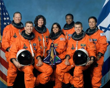 JOHNSON SPACE CENTER, HOUSTON, Texas -- (JSC-STS107-5-002) -- The seven STS-107 crew members take a break from their training regimen to pose for the traditional crew portrait. Seated in front are astronauts Rick D. Husband (left), mission commander, and William C. McCool, pilot. Standing are (from left) astronauts David M. Brown, Laurel B. Clark, Kalpana Chawla and Michael P. Anderson, all mission specialists; and Ilan Ramon, payload specialist representing the Israeli Space Agency.
