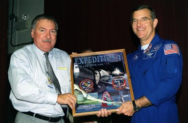"""KENNEDY SPACE CENTER, Fla. -- J.J. """"Tip"""" Talone Jr., director of KSC's International Space Station/Payload Processing, presents Expedition 2 crew member Jim Voss with a photo plaque from employees commemorating his stay aboard the Space Station. The Expedition 2 crew, which included astronaut Susan Helms and cosmonaut Yury Usachev , made the space voyage to the Station on mission STS-102 in March 2001. After five months on the Station, they returned to Earth, at the KSC Shuttle Landing Facility, on mission STS-105 in August 2001"""