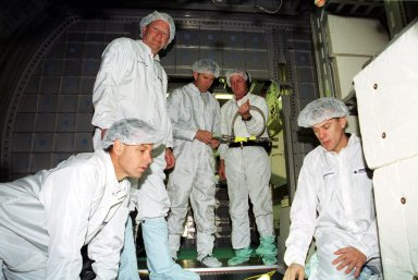 """KENNEDY SPACE CENTER, Fla. -- Inside the Double Module, located at SPACEHAB in Cape Canaveral, Fla., members of the STS-107 crew get training on some of the experiments that will be on their research mission. Kneeling in front are Payload Specialist Ilan Ramon (left) and Pilot William """"Willie"""" McCool; standing behind them are Mission Specialist David Brown and Commander Rick Husband, who is working with a trainer. The mission will be the first flight of the Double Module and will also carry a Hitchhiker payload. The experiments range from material sciences to life sciences (many rats). The Hitchhiker carrier system is modular and expandable in accordance with payload requirements. Hitchhiker experiments are housed in canisters or attached to mounting plates. The Hitchhiker canister comes in two varieties--the Hitchhiker Motorized Door Canister and the Sealed Canisters"""