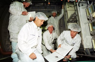 """KENNEDY SPACE CENTER, Fla. - At SPACEHAB in Cape Canaveral, Fla., members of the STS-107 crew get training on experiments in the Double Module, one of the mission payloads. Standing at left is Mission Specialist David Brown; kneeling in front are (left) Payload Specialist Ilan Ramon, from Israel, and Pilot William """"Willie"""" McCool; Commander Rick Husband stands in the background. In the center is a trainer. A research mission, the mission will be the first flight of the Double Module and will also carry a Hitchhiker payload. The experiments range from material sciences to life sciences (many rats). The Hitchhiker carrier system is modular and expandable in accordance with payload requirements. Hitchhiker experiments are housed in canisters or attached to mounting plates. The Hitchhiker canister comes in two varieties--the Hitchhiker Motorized Door Canister and the Sealed Canisters"""