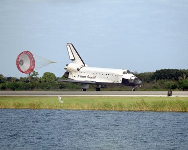 KENNEDY SPACE CENTER, FLA. -- Orbiter Endeavour slows to a stop on Runway 15 at the KSC Shuttle Landing Facility as its drag chute slowly falls to the ground. Completing mission STS-108, Endeavour's main gear touchdown occurred at 12:55:10 p.m. EST (17:55:10 GMT); nose gear touchdown at 12:55:23 p.m. (17:55:23 GMT); wheel stop at 12:56:13 p.m. (17:56:13 GMT). Rollout distance was 8,941 feet. Endeavour carries both the mission crew and the Expedition 3 crew - Commander Frank Culbertson and cosmonauts Vladimir Dezhurov and Mikhail Tyurin - who are returning to Earth after 129 days in space on the International Space Station. The landing is the 57th at KSC in the history of the program STS-108 was the 12th mission to the Space Station. This mission was the 107th flight in the Shuttle program and the 17th flight for the orbiter