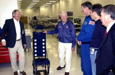 KENNEDY SPACE CENTER, FLA. - During a tour of KSC, former President Jimmy Carter is shown the current version of a lightweight mission specialist seat. From left to right are Ron Woods, a technician in the Flight Crew Equipment Facility; Carter; astronaut Joseph Tanner; another KSC employee; and Tip Talone, director of Payload Processing, International Space Station